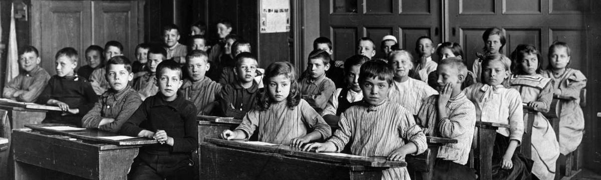 Historisch beeld van een klaslokaal met schoolkinderen